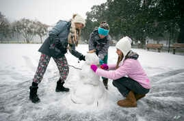 Children from the Hoffman and Lynns families build a snowman on the public basketball courts in Forsyth Park, Jan. 3, 2018, in Savannah, Georgia.