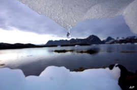 FILE - An iceberg melts in Kulusuk, Greenland near the arctic circle. A new report finds permafrost in the Arctic is thawing faster than ever before.