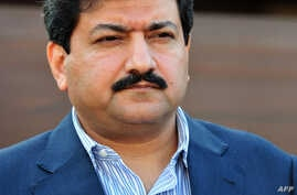 FILE - Pakistani journalist and television anchor, Hamid Mir talks with media representatives outside his home in Islamabad.