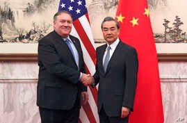 U.S. Secretary of State Mike Pompeo, left, shakes hands with Chinese Foreign Minister Wang Yi before their meeting at the Diaoyutai State Guesthouse in Beijing, Oct. 8, 2018.