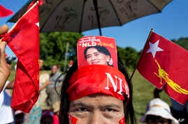 A supporter displays a picture of opposition leader Aung San Suu Kyi stuck in her headband during a campaign rally of the National League for Democracy in Thandwe, Myanmar, Oct. 17, 2015.