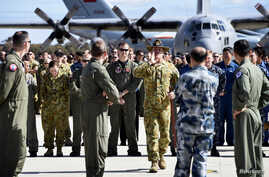 An official yells to members of aircrews, who are involved in the search for missing Malaysia Airlines plane MH370, to get them into position for an official photograph as they stand on the tarmac at the Royal Australian Air Force (RAAF) Pearce Base,