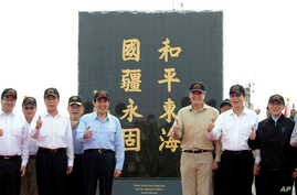 "Taiwan's President Ma Ying-jeou, fifth from left, poses for a group photo in front of a monument reading: ""Peace in the East China Sea and our national territory secure forever"" during his visit to Pengjia Islet in the East China Sea, north of Taiwan"