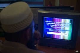 FILE - A Pakistani viewer looks at a television screen flashing suspension notice of GEO News channel in Islamabad, Pakistan, June 6, 2014.