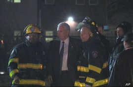 Republican presidential candidate Indiana Gov. Mike Pence talks with firefighters at New York's LaGuardia Airport after his campaign plane slide off the runway while landing, Oct. 27, 2016.