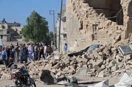 Residents look at the damage at a site hit by what activists said was a barrel bomb dropped by forces of Syria's President Bashar al-Assad, in the old city of Aleppo, May 31, 2015.