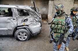 Security forces inspect the site of a car bomb attack in Baghdad's Karrada neighborhood, Iraq, Nov. 20, 2013.