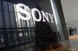 FILE - The logo of Sony Corp and a Christmas tree are reflected on the company's 4K television set at the company's headquarters in Tokyo Nov. 18, 2014.