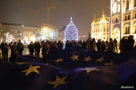 "People hold a big European Union flag during a protest against a proposed new labor law, billed as the ""slave law,"" in front of the Parliament building in Budapest, Hungary, Dec. 18, 2018."