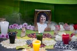 FILE - A framed image of environmentalist Berta Caceres on a makeshift altar made in her honor during a demonstration outside Honduras' embassy, in Mexico City, June 15, 2016.