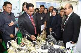 Attendees at the 3R Forum look at toy motorcycles made from recycled parts, Surabaya, Indonesia. (Petrus Riski/VOA)