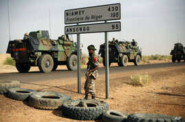 FILE - French armored vehicles heading towards the Niger border before making a left turn north in Gao, northern Mali.