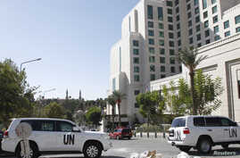 United Nations (U.N.) vehicles are parked in front of the Four Seasons hotel, where a team of experts from the Organisation for the Prohibition of Chemical Weapons (OPCW) are staying, in downtown Damascus, Oct. 22, 2013.