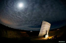 FILE - Light from a full moon is reflected off the Interstellar Light Collector (R) onto people in a moveable trailer (C) in the Sonoran desert near Three Points.