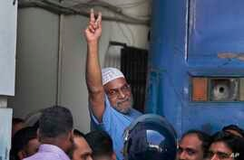 Mir Quashem Ali, a senior leader of the Bangladesh's largest Islamist party Jamaat-e-Islami shows victory sign as he enters a police van after a special tribunal sentenced him to death in Dhaka, Bangladesh,  Nov. 2, 2014.