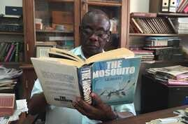 Louis Mukwaya, mosquito researcher at the Uganda Virus Research Institute near Entebbe, reads at his desk about his primary subject of study. (J. Craig/VOA)