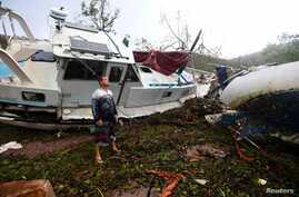 Local resident Bradley Mitchell inspects the damage to a relative's boat after it smashed against the bank after Cyclone Debbie passed through the township of Airlie Beach, located south of the northern Australian city of Townsville, March 29, 2017.