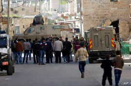 Israeli security forces stand guard as Jewish settlers are forced out of two homes in the West Bank city of Hebron, Jan. 22, 2016.