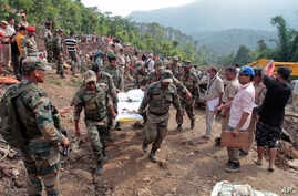 Army soldiers and rescue workers recover bodies of landslide victims even as they try to pull out two buses that were covered in mud after a landslide triggered by heavy monsoon rain in Urla village, Himachal Pradesh state, India, Aug. 13, 2017.