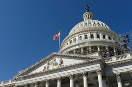 FILE - an American flag flies over Capitol Hill in Washington.