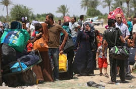 In this Saturday, May 16, 2015 photo, Iraqis fleeing from their hometown of Ramadi, Iraq, rest near the Bzebiz bridge, 65 kilometers (40 miles) west of Baghdad.