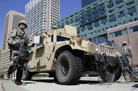 Maryland National Guardsmen patrol near downtown businesses in Baltimore, April 28, 2015, a day after looting and arson erupted following the funeral of Freddie Gray.