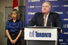 Toronto Mayor Rob Ford speaks at a news conference with his wife Renata (L) at City Hall, Nov. 14, 2013.