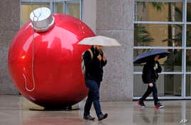 A man and a woman walk in the rain past a holiday ornament, Nov. 29, 2018, in San Francisco. A storm moving into California  brought rain that threatened to unleash debris flows in wildfire burn areas.