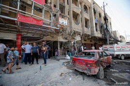 People gather at the site of a car bomb attack in Baghdad's al-Shaab district, August 28, 2013.