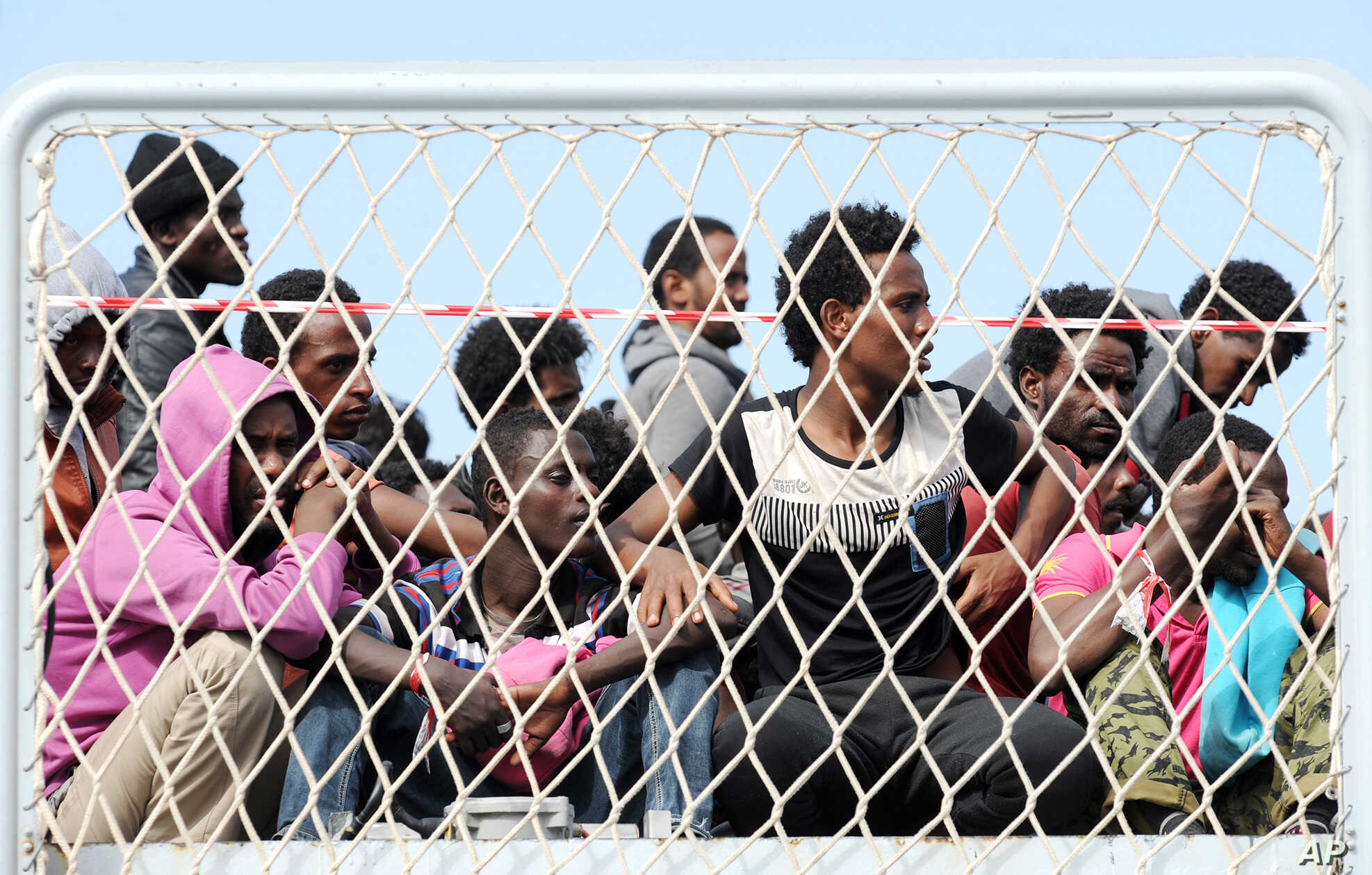 FILE - Migrants wait to disembark from the Italian Navy vessel 'Bettica' in the harbor of Salerno, Italy, May 5, 2015.