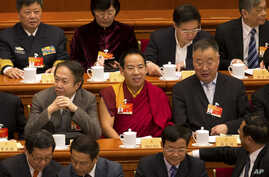 FILE - Gyaltsen Norbu, the Chinese government-appointed 11th Panchen Lama, center, sits with fellow delegates before the closing ceremony of the Chinese People's Political Consultative Conference (CPPCC) at the Great Hall of the People in Beijing, Ma
