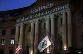 FILE - Light is projected by the League of Conservation Voters as part of the new Boot Pruitt campaign onto the Ronald Reagan Building and International Trade Center, the location of the Environmental Protection Agency, March 28, 2018, in Washington.