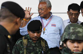 People's Democratic Reform Committee (PDRC) leader Suthep Thaugsuban (C) waves to media as he leaves the criminal court in Bangkok, May 26, 2014.