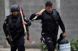 Police carry tools, including axes and a large plier, to use in an operation that aims to rescue four jail guards who were taken in the midst of a prison riot at the Centro Correccional Etapa II reformatory in San Jose Pinula, Guatemala, March 20, 20