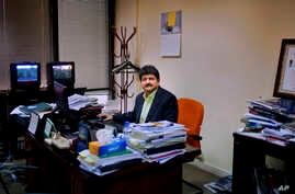 Pakistani journalist Hamid Mir sits in his office in Islamabad, Pakistan. Perhaps the most popular of Pakistan's news anchors, Mir, says both media owners and journalists operate under a cloud of fear, March 14, 2017.