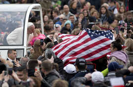 Faithful display a flag of the United States as Pope Francis kisses an infant from his pope-mobile during his tour through the crowd for his weekly general audience in St. Peter's Square at the Vatican, March 23, 2016.