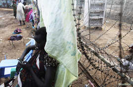 A South Sudanese woman displaced by the fighting uses her phone as she leans against a barbed wire in a camp for displaced persons in the UNMISS compound in Tongping in Juba February 19, 2014. Thousands of people have been killed and more than 800,00
