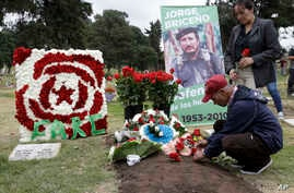 A man places flowers on the grave of slain rebel leader Jorge Briceno, known as Mono Jojoy, during an homage by former members of the Revolutionary Armed Forces of Colombia, FARC, to one of their most prominent =military strategists at a cemetery in