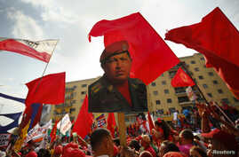A supporter of Venezuela's President Nicolas Maduro holds up a picture of late president Hugo Chavez during a May Day demonstration in Caracas, May 1, 2014.
