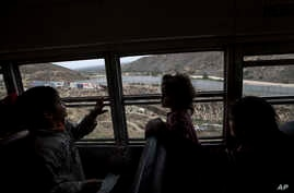 FILE - Central American children who are traveling with a caravan of migrants, look at the border wall from a bus carrying the group to a gathering of migrants living on both sides of the border, in Tijuana, Mexico, April 29, 2018. U.S.