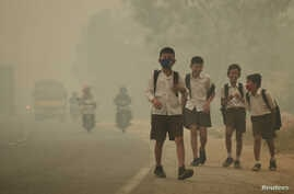 FILE - Students walk along a street as they are released from school to return home earlier due to the haze in Jambi, Indonesia's Jambi province, Sept. 29, 2015, in this picture taken by Antara Foto.