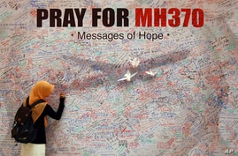 A woman writes a message for passengers aboard a missing Malaysia Airlines plane, at a shopping mall in Kuala Lumpur, Malaysia, March 15, 2014.