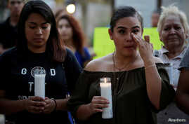 Jennifer Hernandez (L) and Paola Rodriguez, Deferred Action for Childhood Arrivals (DACA) program recipients, participate in a candle vigil at the San Jacinto Plaza in El Paso, Texas, Sept. 5, 2017.