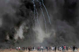 Palestinian protesters gather in front of burned tires while Israeli soldiers fire teargas during clashes with Israeli troops along Gaza's border with Israel, east of Khan Younis, Gaza Strip, Friday, April 6, 2018.