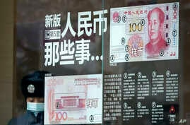 FILE - A security guard wearing a protection mask against air pollution takes a rest near a bank window panel displaying the security markers on the latest Yuan note in Beijing, Jan. 1, 2017.