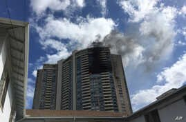 Smoke billows from a high-rise apartment building in Honolulu, July 14, 2017. Dozens of firefighters are battling the multiple-alarm fire at Marco Polo apartments that Honolulu Fire Department spokesman Capt. David Jenkins said started on the 26th fl