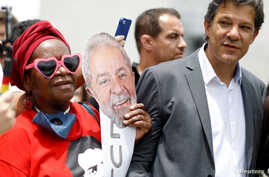 A supporters of former Brazil's President Luiz Inacio Lula da Siva holds a mask next to Fernando Haddad next to the Federal Justice headquarters in Curitiba, Brazil, Nov. 14, 2018.