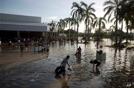 People wade through waist-high water in a store's parking, looking for valuables, south of Acapulco, in Punta Diamante, Mexico, Wednesday, Sept. 18, 2013. Mexico was hit by the one-two punch of twin storms over the weekend, and the storm that soaked
