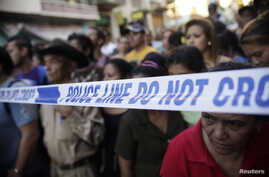 People stand behind a police line at a crime scene in Tegucigalpa, Honduras, Nov. 19, 2013.