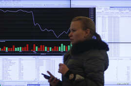 A woman walks past an information screen inside the office of the Moscow Exchange on March 14, 2014. Russian stock indexes have plunged in recent months.